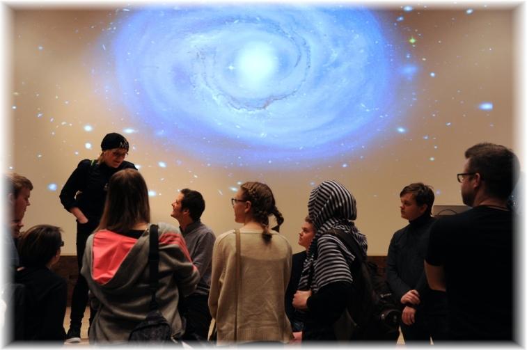 """Christophe Galfard sitter på scenkanten, besvarar frågor och samtalar med eleverna som fått ta del av hans föreläsning """"The Universe in Your Hand"""" Han tar sig tid för morgondagens forskare."""